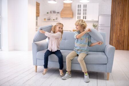 Home entertainment. Two kids beating each other with pillows and feeling enjoyed Archivio Fotografico