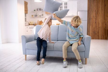 Games at home. Two kids beating each other with pillows and feeling angry