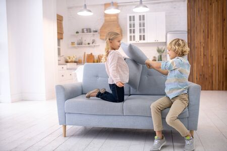 Games. Two kids beating each other with pillows and looking involved