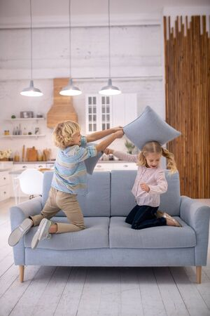 Having fun. Blond cute boy putting a pillow on his sisters head