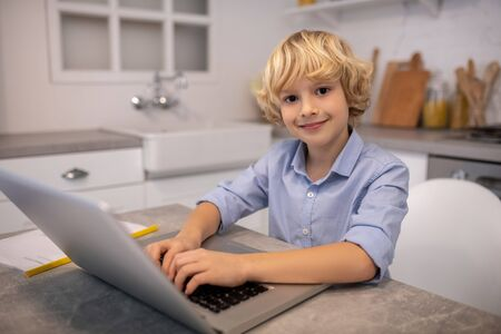 Positive mood. Cute blond boy typing on a laptop and smiling