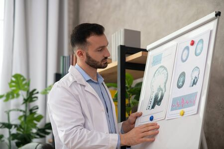 Analyzing drawings. Young bearded doctor in a white robe looking involved working with drawings