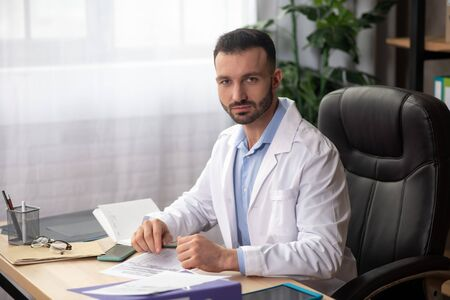 In the office. Young bearded doctor in a white robe sitting at the table in his office Reklamní fotografie