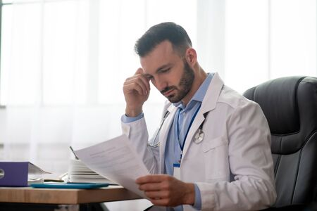Important report. Young bearded doctor in a white robe reading