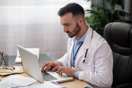 Busy at work. Young bearded doctor in a white robe looking busy
