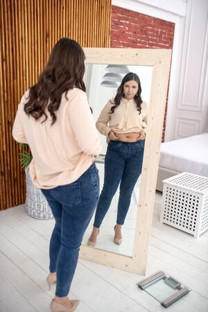 Large build. Young woman in a beige blouse looking at herself
