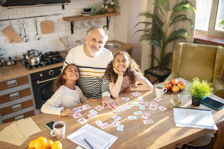 Cute kids. Two dark-skinned girls playing words game with their granddad and looking smiling