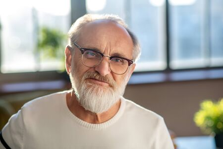 Good mood. Close up picture of grey-haired bearded man in eyeglasses smiling nicely