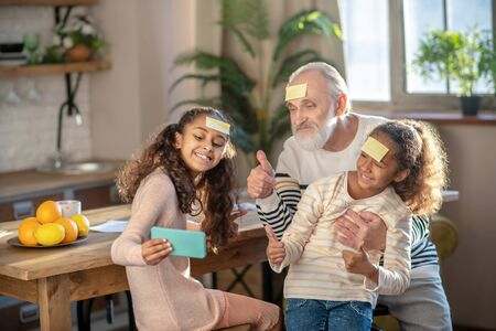Happy day. Grey-haired bearded man and his granddaughters looking joyful