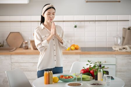 Self-knowledge. Calm young Asian girl standing closing her eyes clasped her hands in the kitchen near the table with vegetarian products.