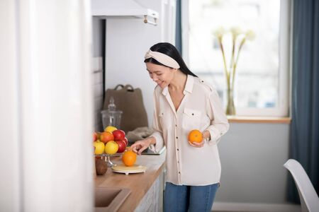 Citrus fruits. Cute young girl standing holding an orange in her hand looking at the table, smiling in a good mood.