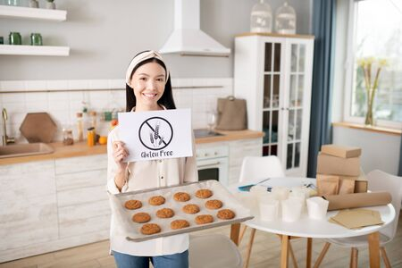Gluten free baking. Young girl with a tray of fresh homemade pastries and a poster without gluten in her hands, standing smiling in a cheerful mood.