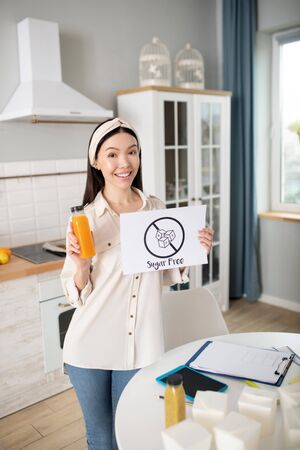 Delicious healthy juice. Young girl with a bottle of orange juice and a poster with the words in her hands, standing in a good mood.