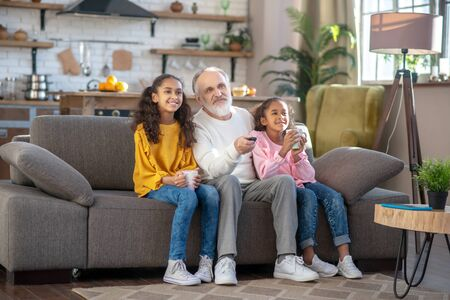 Weekend. Two dark-skinned girls and their granddad watching tv together while sitting on the sofa