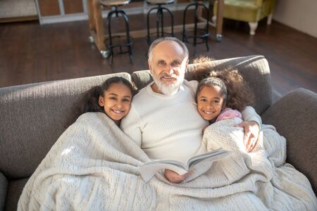 Comfort. Grandfather and his two grandaughters sitting on the sofa and feeling comfortable