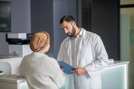 Talking to doctor. Tall male young doctor talking to a female patient in clinic
