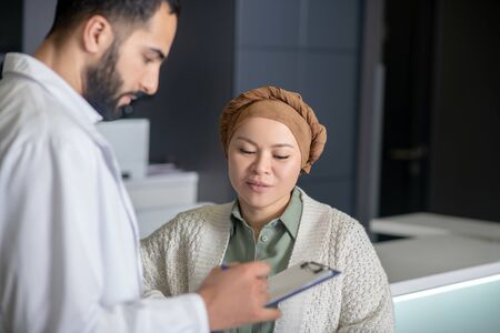 Making an appointment. Tall male young doctor talking to a female patient
