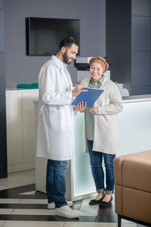 Appointment. Tall male doctor talking to a female patient