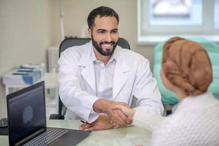 Doctors office. Dark-haired male doctor holding his female patients hands