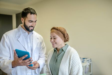 Information from internet. Bearded young doctor showing something on the tablet to his patient Banque d'images