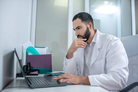 Looking serious. Male doctor in a white robe working at laptop looking serious