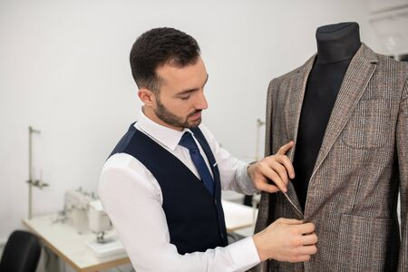 Fashion design studio. Male fashion designer undoing buttons of grey jacket Imagens