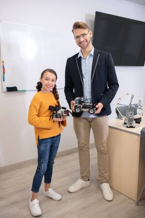 School classroom. Male teacher and dark-haired girl standing at the desk, holding buildable cars, smiling