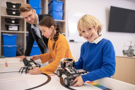 School classroom. Pupils playing with buildable cars, blond boy showing his, smiling, teacher and dark-haired girl discussing something