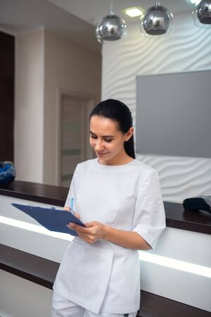 Receptionist working. Hard-working receptionist of beauty clinic making notes of appointments