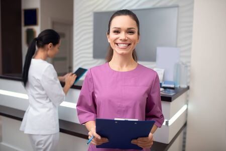 Smiling broadly. Beaming woman wearing uniform working in beauty clinic smiling broadly