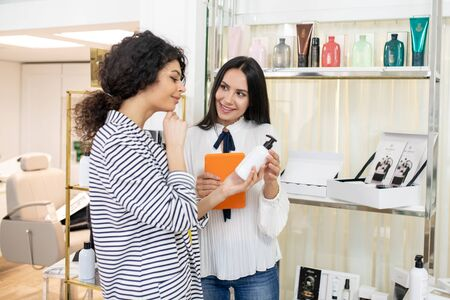New product. Dark-haired shop assistant offering new body care products to the customer