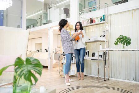 Talking. Two dark-haired women talking in the beauty shop