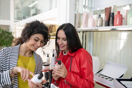 Hair care products. Two beaming ladies choosing hair care products