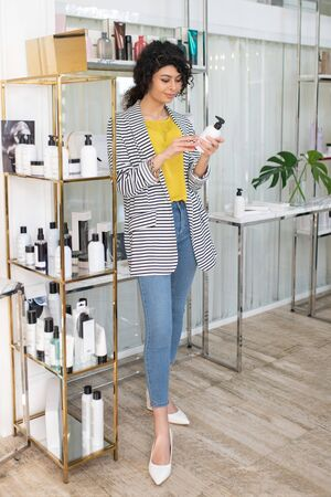 New product. Dark-haired beautiful woman holding body lotion in her hands 写真素材