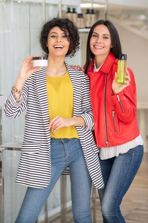 Body treatment. Two good-looking dark-haired girls showing body care products 写真素材