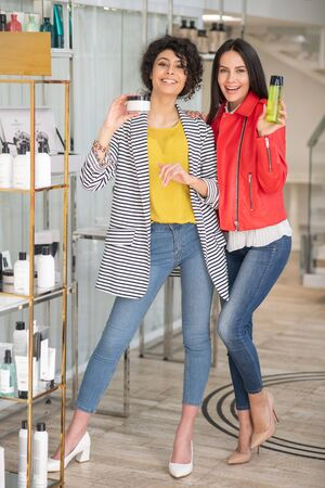 Beauty shop. Two good-looking girls choosing beauty products