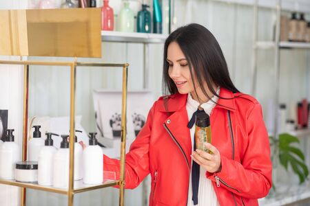 At beauty store. Dark-haired woman choosing body care products in a beauty store