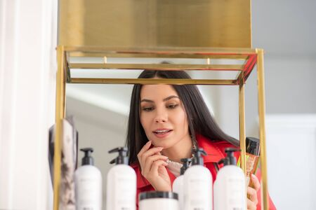 What to buy. Dark-haired pretty woman choosing body care products