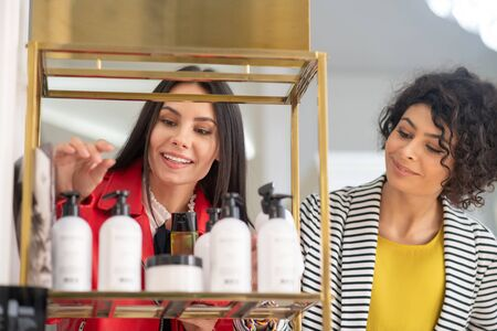 Body care. Two pretty women choosing body care products