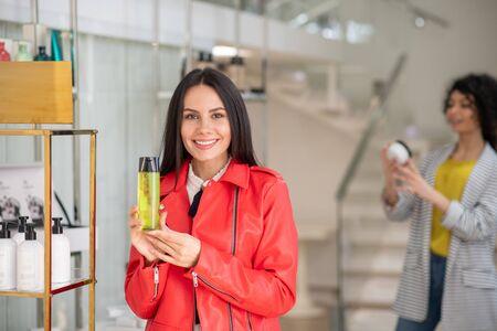 Feeling excited. Brunette woman in a red jacket choosing a shower gel