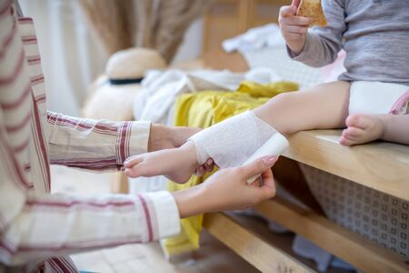 At home. Woman hands applying bandage on child's leg Banque d'images