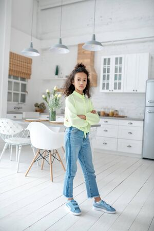 Pretty girl. Curly- haired girl with in jeans standing with arms crossed