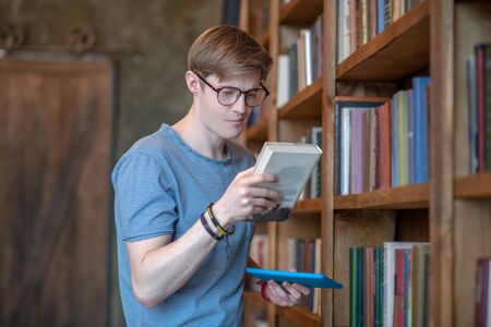 Love reading. Young man in eyewear reading the title of the book