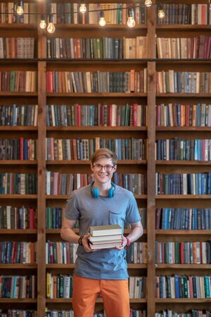 In the library. Fair-haired young man in eyeglasses standing in the library