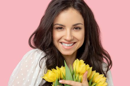 Wide smile. Young pretty dark-haired woman holding yellow flowers and smiling