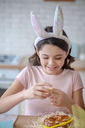 Busy nd enjoyed. Sweet girl wearing easter bunnys ears holding easter bun in her hands Stock fotó