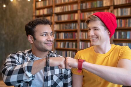 Good mood. Two young handsome men putting fist to fist and smiling