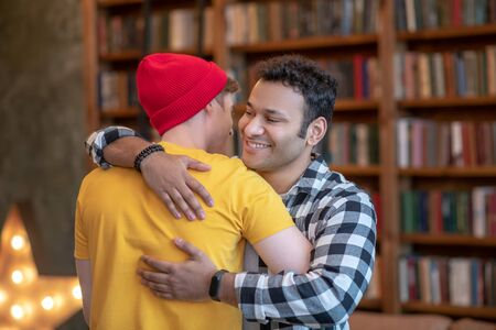 Glad to see you. Two young handsome men hugging each other and smiling