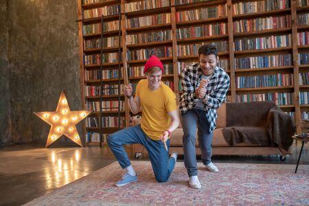 Having fun. Young man in a yellow tshirt having fun with his friend