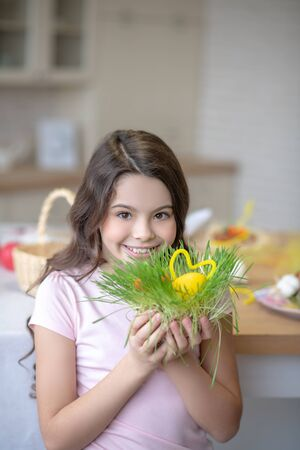 Easter time. Pretty smiling girl holding in hands easter decorations